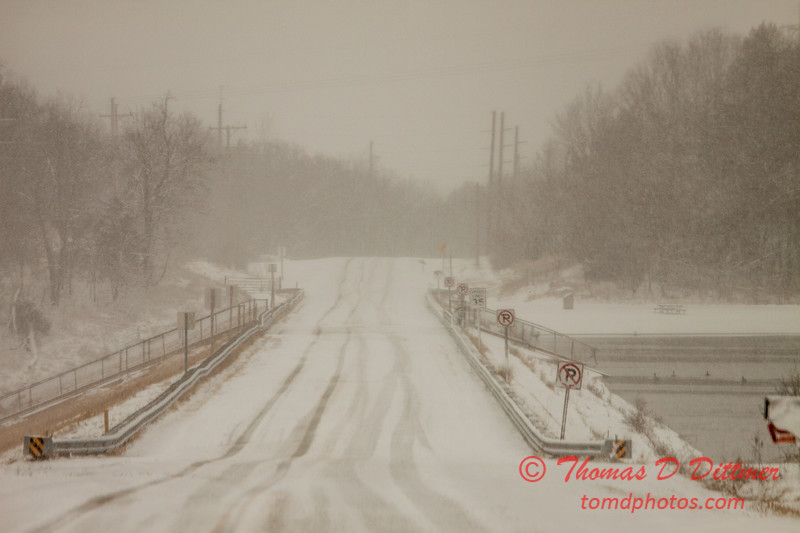 # 28 - Snow falling covers the roadway over the dam at Evergreen Lake Hudson Illinois