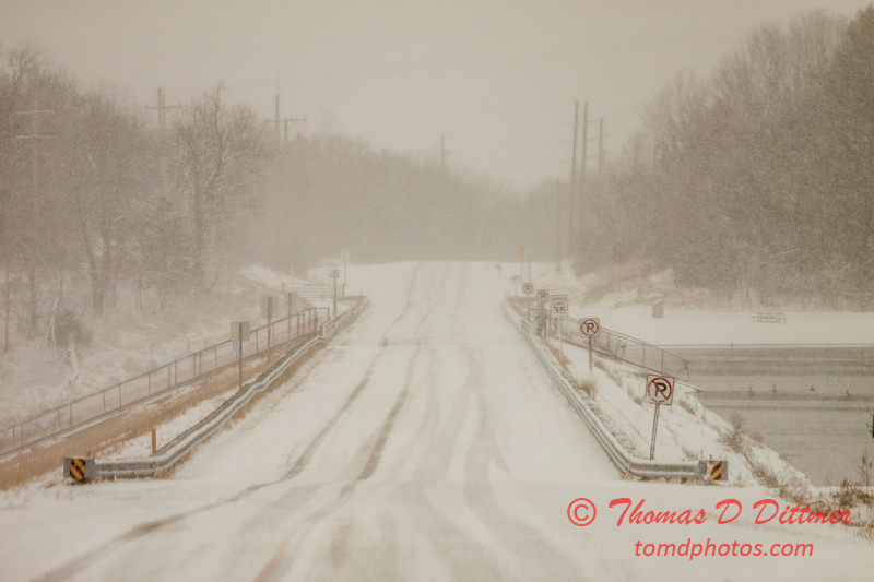 # 29 - Snow falling covers the roadway over the dam at Evergreen Lake Hudson Illinois