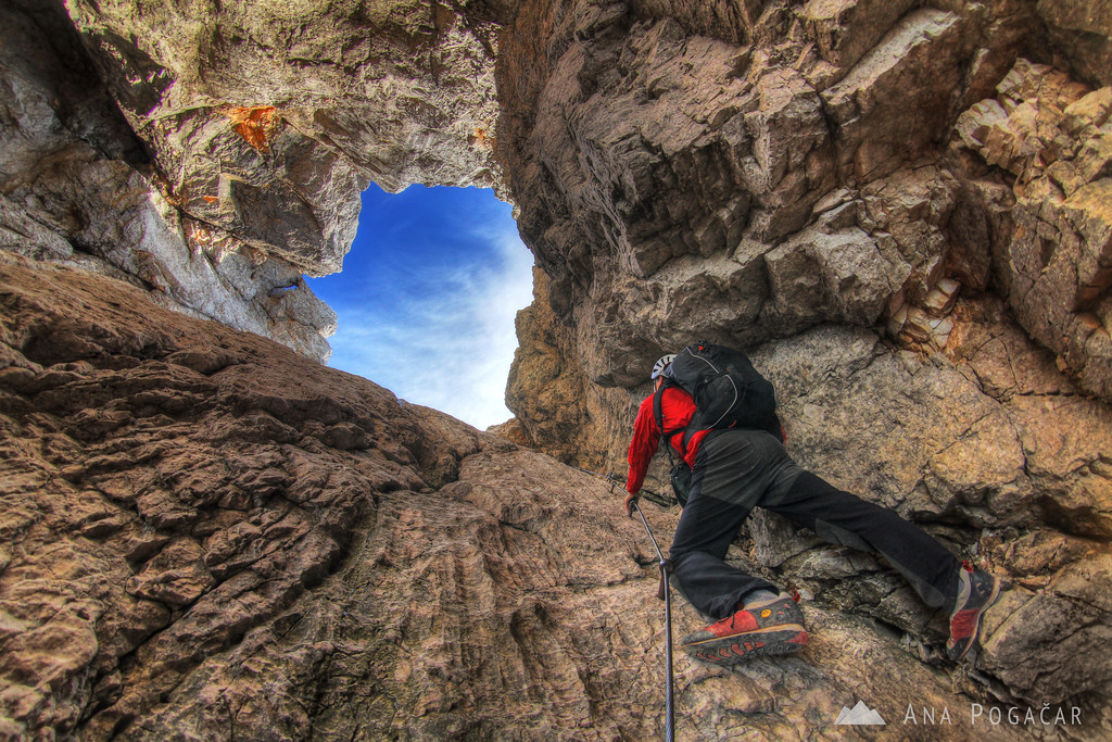 Climbing through the natural window in the north face of Mt. Prisojnik