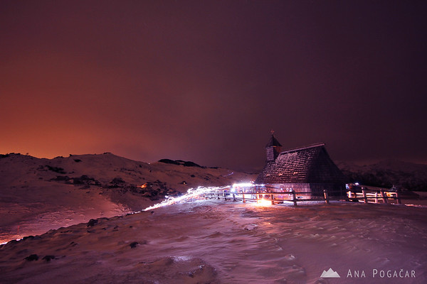 Procession of people hiking with torches to the Velika planina chapel for the Christmas midnight mass
