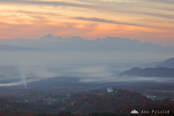 Views from Špica hill: St. Ana church in Tunjice and Mt. Triglav in the background