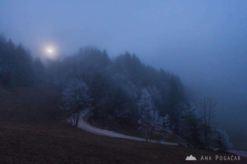 Full moon through the fog at the bottom of Kamniški vrh hill