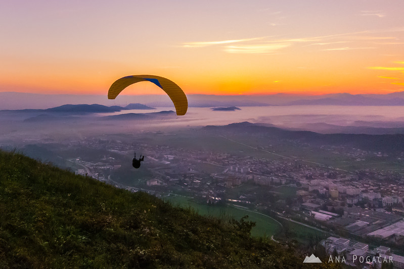 A paraglider gliding into the sunset from Špica hill