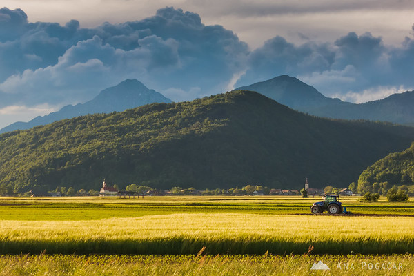 A tractor and ominous clouds above Mt. Krvavec