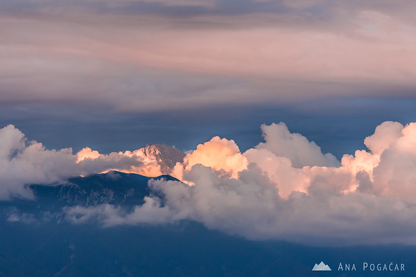 Last sun rays on the Kamnik Alps with some ominous clouds in the background, as seen from Jamnik.