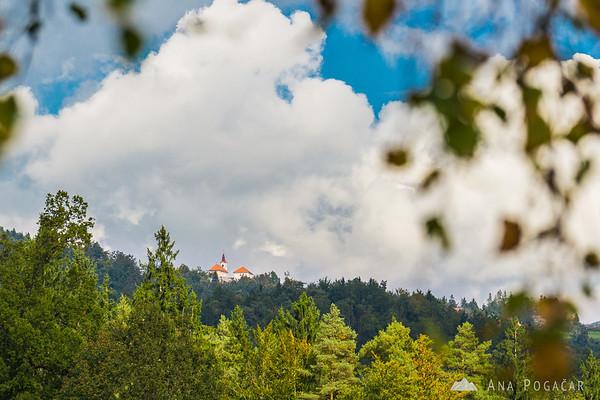 Biking around Kamnik through villages and across fields - looking at the church at Šenturška gora from Glinje