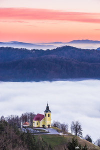 Yellow church in Češnjice above the fog at sunset