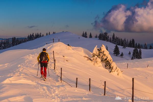 A lonely hiker at Poljanski rob on Velika planina at sunset