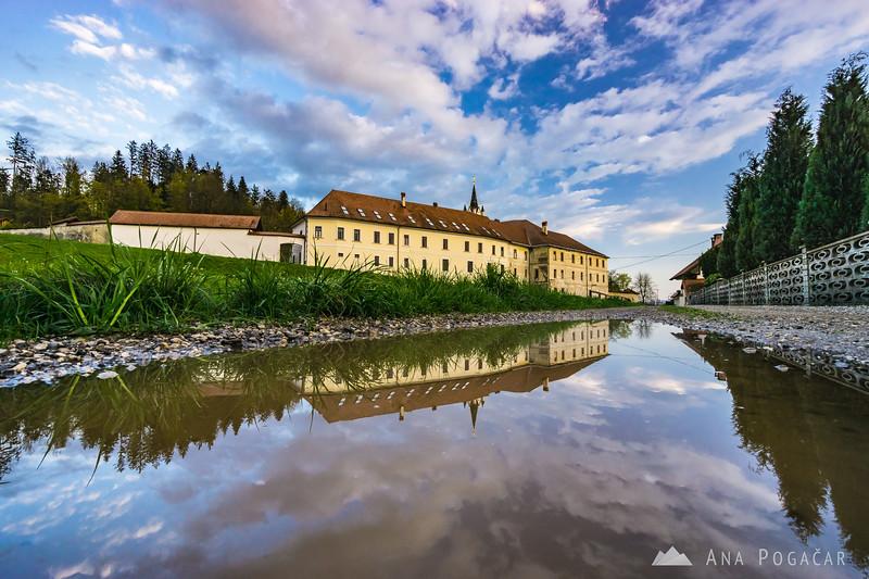 Mekinje monastery reflected in a puddle