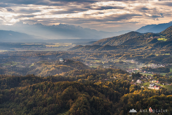 St. Ana church in Tunjice and the Julian alps with Mt. Triglav from Špica hill above Kamnik