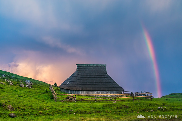 Rainbow over Velika planina and stormy sunset clouds