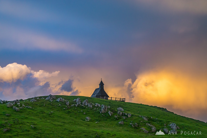 Chapel on Velika planina and stormy sunset clouds