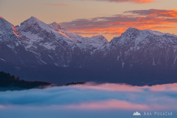 First sun rays illuminate the clouds above the Kamnik Alps