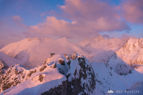 Winter ascent to Mt. Viševnik - pink Julian Alps with Mt. Triglav.