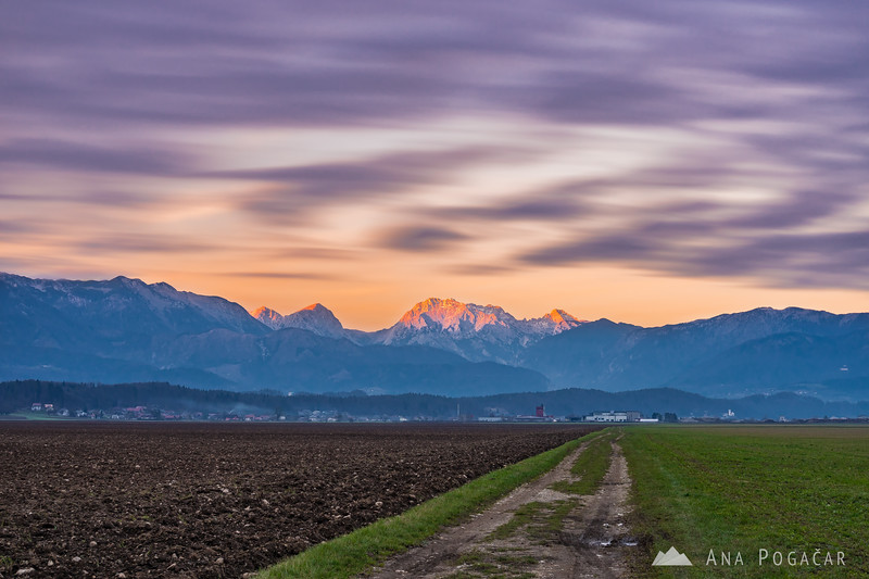 Long-exposure shot of clouds moving over the Kamnik Alps at sunset
