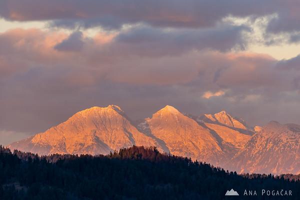 The Kamnik Alps glowing in the sunset light as seen from Smrečje in the Polhograjsko hribovje hills: Mts. Kočna, Grintovec, Skuta and Kalški greben