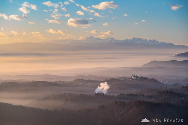 St. Ana church in Tunjice and the Julian Alps in the background from Špica hill above Kamnik