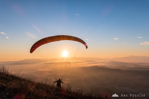 A paraglider taking off from Špica into the sunset