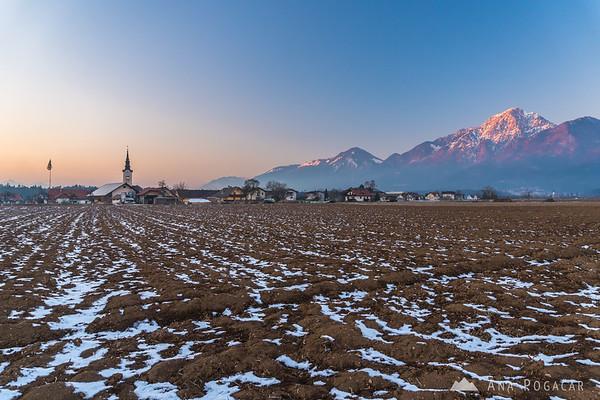 Hotemaže village and Mt. Storžič after sunset on a cold winter day