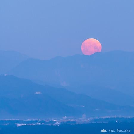 Full moon setting as seen from Stari grad above Kamnik