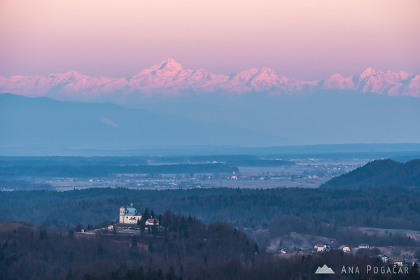 St. Ana church in Tunjice and the Julian Alps with Mt. Triglav in the background at sunrise