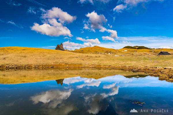 Chapel on Velika planina reflected in a waterhole