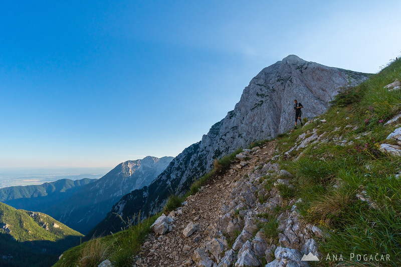 A hiker descending from the Kamnik Saddle, with Mt. Brana in the background