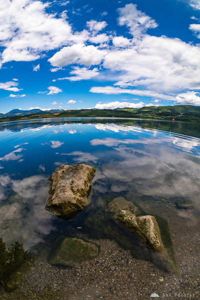 Crazy reflection of a blue sky with puffy white clouds in Velenje Lake