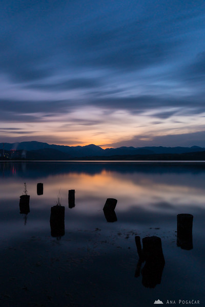A long-exposure shot of the clouds moving over Velenje Lake at sunset