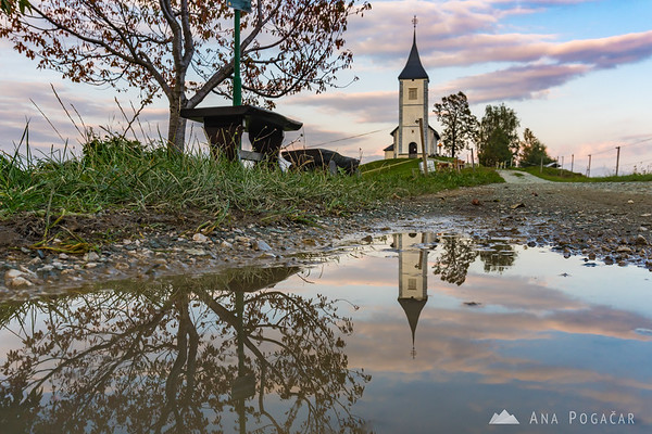 Jamnik church reflected in a puddle