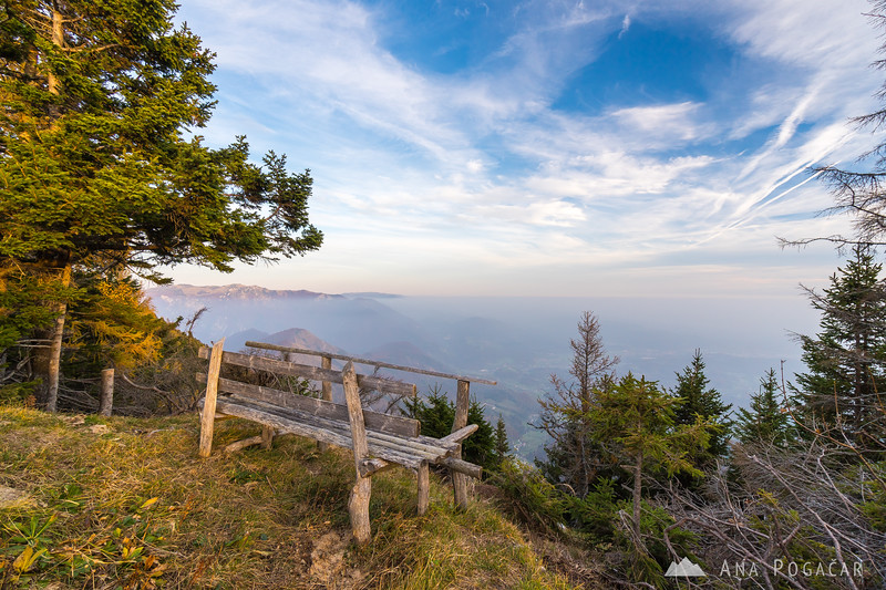 A bench on Mt. Kržišče with a view of Kamniški vrh and Velika planina
