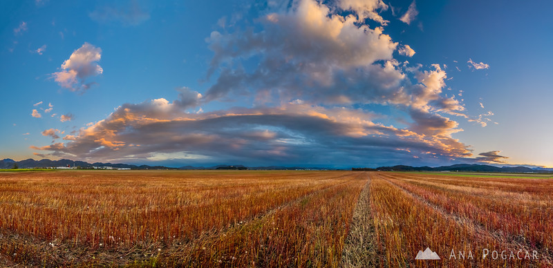 Stitched panorama of the sunset clouds over fields near Kamnik