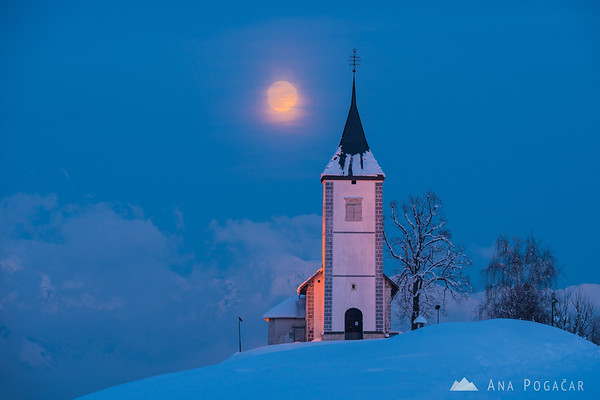 Full moon rising from above the church in Jamnik