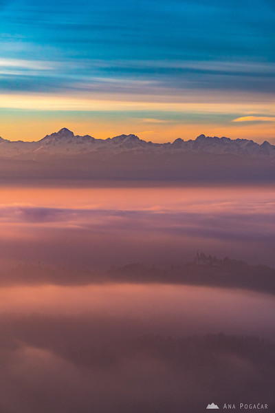 Mt. Triglav and the Julian Alps above the fog and the St. Ana church in Tunjice