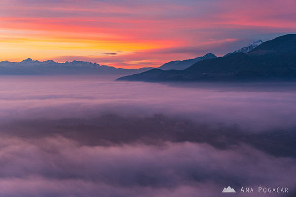 Kamnik hiding in the fog as sunset colors adorn the winter sky