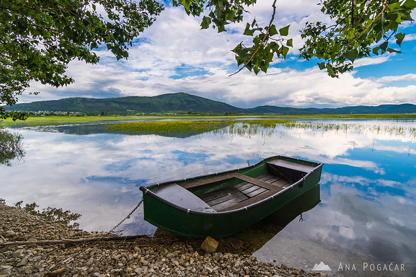 A boat on Lake Cerknica, with Mt. Slivnica in the background