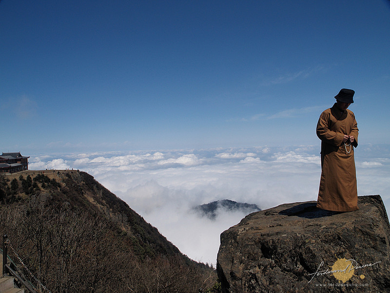 Praying monk on a high at the summit of Emeishan China. Standing on the Cliff of Self Sacrifice