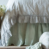 Linen Whisper Duvet Cover in Cloud, Linen Bed Skirt in Thyme, Olivia Bolster in Thyme over Linen Bolster in Cloud
