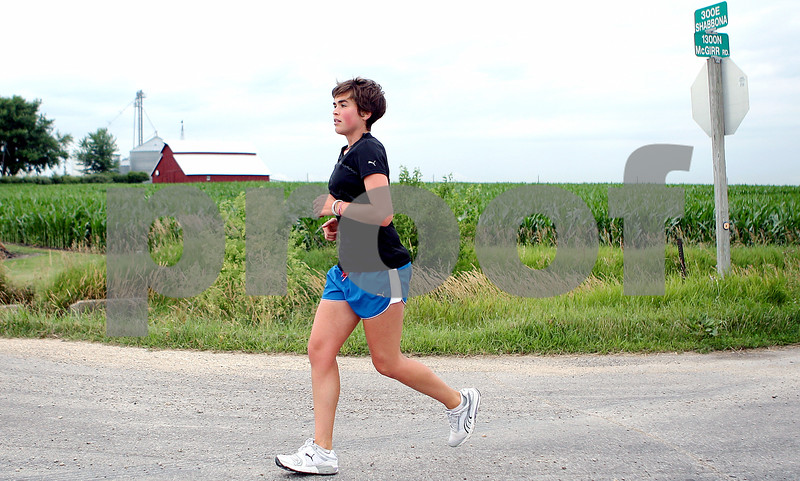 Rob Winner – rwinner@daily-chronicle.com<br /> Katie Visco crosses Shabbona Road while running west on McGirr Road in DeKalb County on Wednesday morning. Visco, who is running across the United States, began her journey in Boston back on March 29th.<br /> 07/08/2009