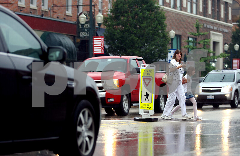 Rob Winner – rwinner@daily-chronicle.com<br /> Tammy Newsome and her daughter, Rhiannon, 8, of Lake in the Hills, cross State Street at Maple Street, as vehicles yield, on their way to the DeKalb County Courthouse in Sycamore on Friday morning.<br /> 07/10/2009<br /> CQ names
