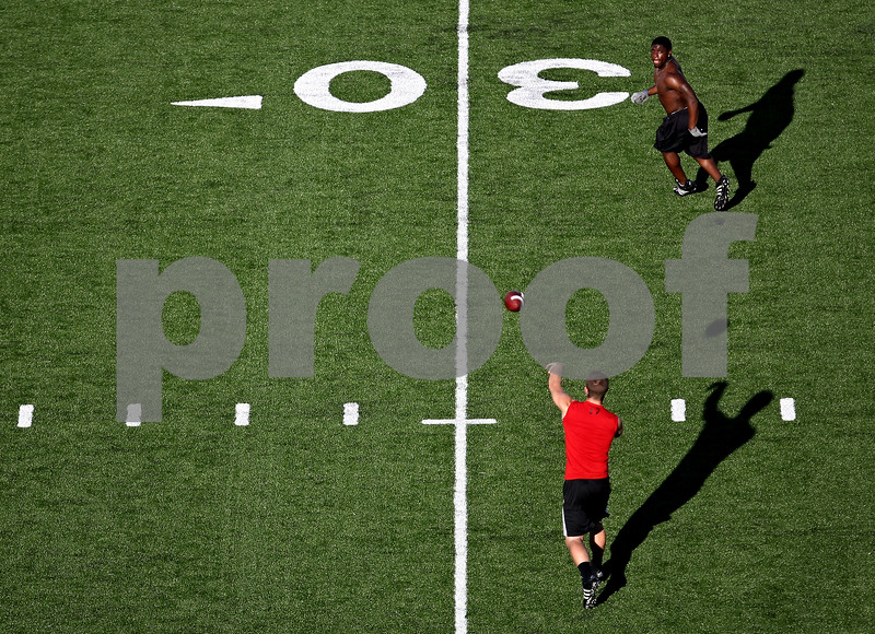 Beck Diefenbach  -  bdiefenbach@daily-chronicle.com<br /> <br /> Northern Illinois quarterback A.J. Hill passes the ball to Chad Spann during practice at Huskie Stadium in DeKalb, Ill., on Wednesday June 24, 2009.