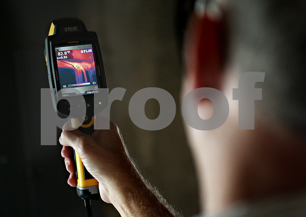 Beck Diefenbach  -  bdiefenbach@daily-chronicle.com<br /> <br /> Ken Spears, of Ken Spears Construction, demonstrates how he uses a heat sensor camera to search out air leaks in a home during an air sealing audit in a Sycamore home on Monday Sept. 15, 2009.