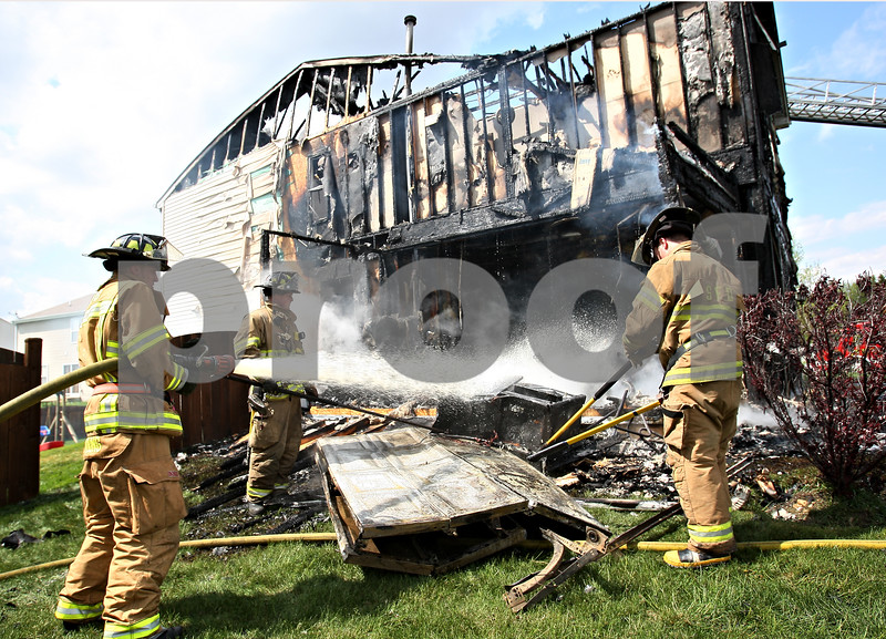 Beck Diefenbach  -  bdiefenbach@daily-chronicle.com<br /> <br /> Sycamore firefighters cover hot spots at a house at 800 Willow Rd. in Kirkland, Ill., on Monday May 11, 2009.