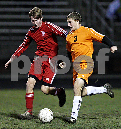 Rob Winner – rwinner@daily-chronicle.com<br /> In the first half, Marian's Nick Pierce (left) chases after DeKalb's Sam Dumbacher during the IHSA Class 2A Freeport Sectional semifinal in Belvidere on Tuesday October 27, 2009. DeKalb defeated Marian, 1-0.