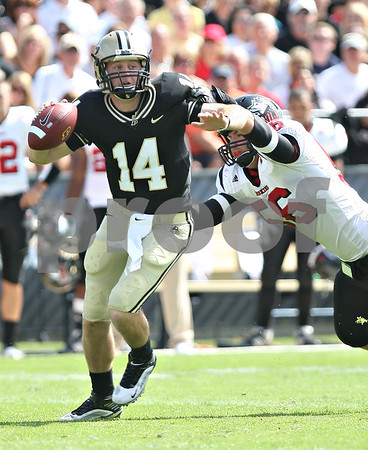 Beck Diefenbach – bdiefenbach@daily-chronicle.com<br /> <br /> Northern Illinois' Brandon Bice (56) tackles Purdue quarterback Joey Elliot (14) during the first half of the game in West Lafayette, Ind., on Saturday Sept. 19, 2009