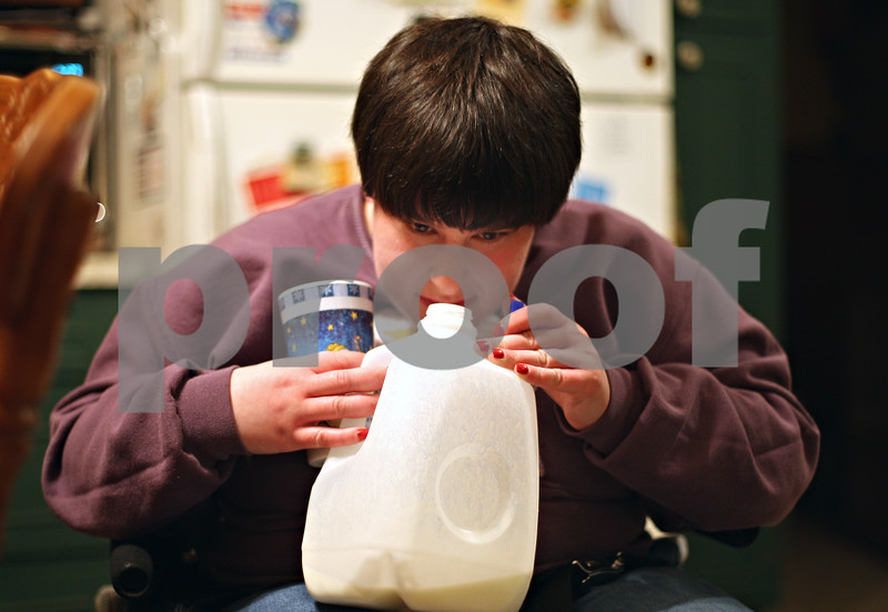 Beck Diefenbach – bdiefenbach@daily-chronicle.com<br /> <br /> Emily Lampkin, 20, of Sycamore, smells milk she thinks has gone sour as she prepares dinner for her family at her home in Sycamore, Ill., on Thursday Feb. 19, 2009. Emily, who lives with Spina Bifida and Shunted Hydrocephalus, practices at home what she has learned at Life School.