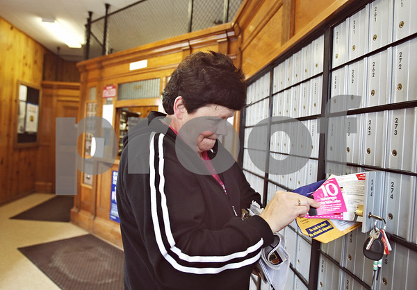 Beck Diefenbach – bdiefenbach@daily-chronicle.com<br /> <br /> Sharon Rissman, of Waterman, collects her mail from her Post Office Box at the Waterman Post Office in Waterman, Ill., on Tuesday March 10, 2009. Rissman checks her box only three days of the week and doesn't believe a cut in delivery service would effect her that much.
