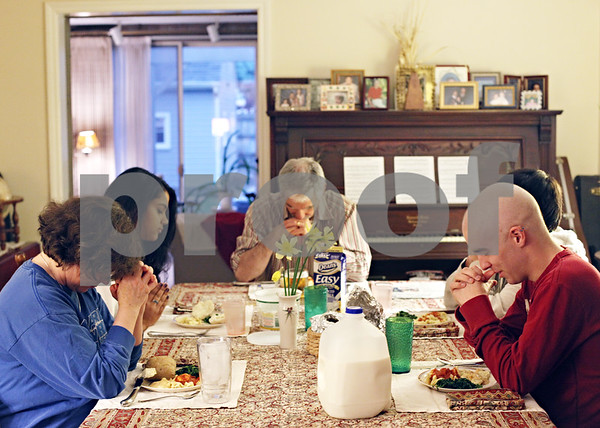 Beck Diefenbach  -  bdiefenbach@daily-chronicle.com<br /> <br /> Kevin, right, prays with his family before dinner at their home on Tuesday April 14, 2009.