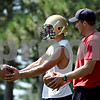 Rob Winner – rwinner@daily-chronicle.com<br /> Jace Quimby works with assistant coach Tyler Whitebread during a recent Hiawatha football practice.<br /> 08/12/2009