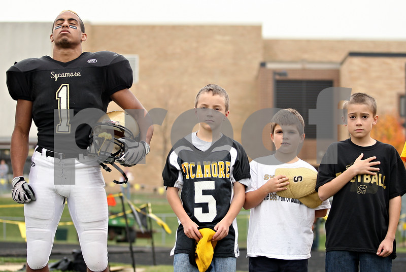 Beck Diefenbach  -  bdiefenbach@daily-chronicle.com<br /> <br /> Sycamore water boys stand by Sycamore running back Marckie Hayes (1, left) during the singing of the National Anthem before the start of the playoff game against Montini at Sycamore High School in Sycamore, Ill., on Saturday Nov. 14, 2009.